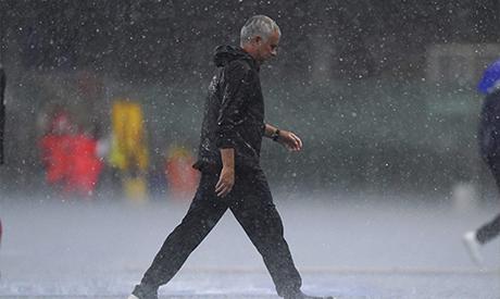 Roma coach Jose Mourinho runs under pouring rain during a Serie A soccer match between Hellas Verona