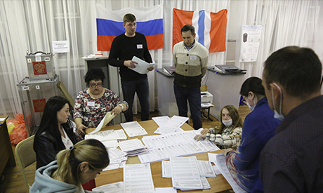 Members of an election commission count ballots after voting at a polling station after the Parliame