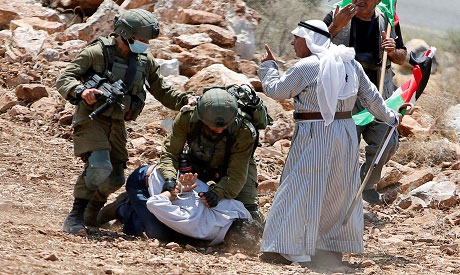 Israeli soldiers detain a Palestinian
