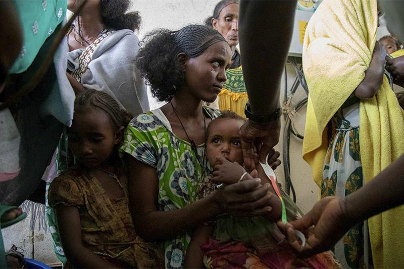 A woman holds a child during a screening for malnutrition in pregnant and lactating women by UNICEF