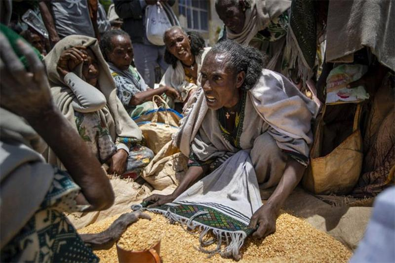 An Ethiopian woman argues with others over the allocation of yellow split peas after it was distribu