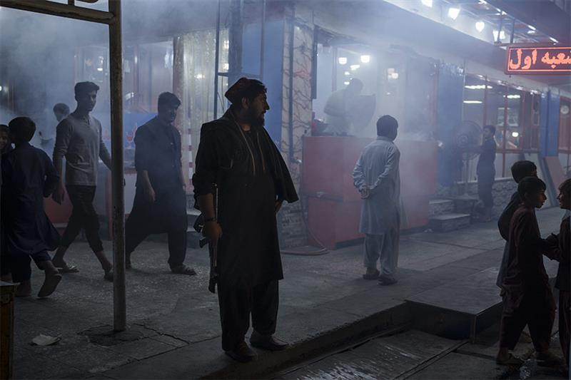 An armed Taliban fighter stands in the corner of a busy street at night in Kabul, Afghanistan, Frida