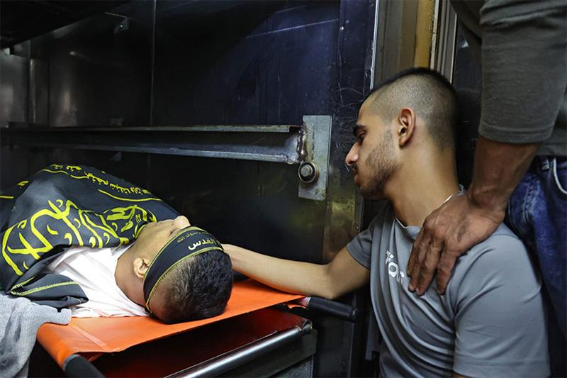 A mourner looks at the body of Osama Soboh, a Palestinian man killed by Israeli soldiers during clas